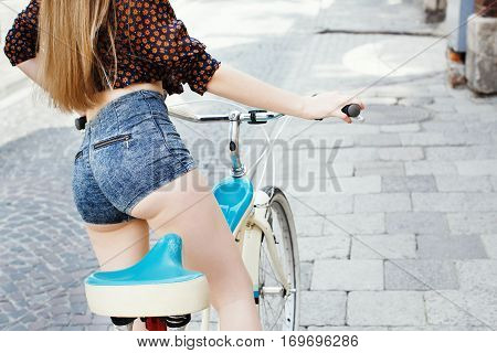 Rear view of young girl which wearing on dark blouse and blue shorts with long fair hair is sitting on bicycle on the street of old European city .