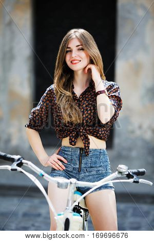 Smiling pretty girl wearing on dark blouse and blue shorts with long straight fair hair is posing on the bicycle on the street of old city.