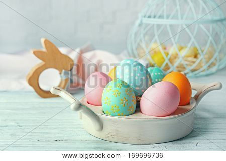 Bowl with colourful Easter eggs on white wooden table