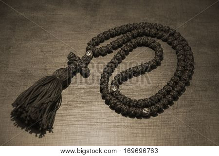 Black rosary on wooden table - toned image