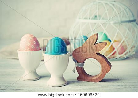 Easter eggs and rabbit figure on white wooden table