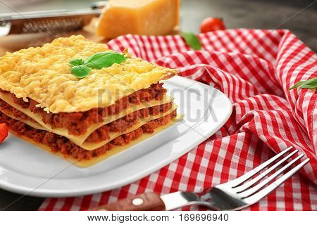 Plate with tasty lasagna on napkin. Closeup