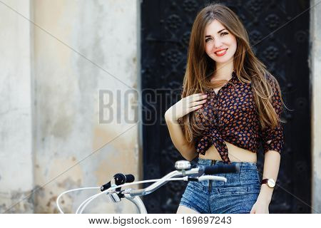 Happy young woman with long straight fair hair wearing on dark blouse and blue shorts is sitting on the bicycle and looking at camera on the street of old European city.
