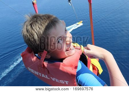 Happy boy parasailing high over the sea. The boat cuts a water smooth surface far below. Having fun. Positive human emotions feelings joy.