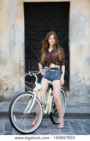 Pretty girl wearing on dark blouse and blue shorts with long straight hair is posing on bicycle on the street of old city, full body