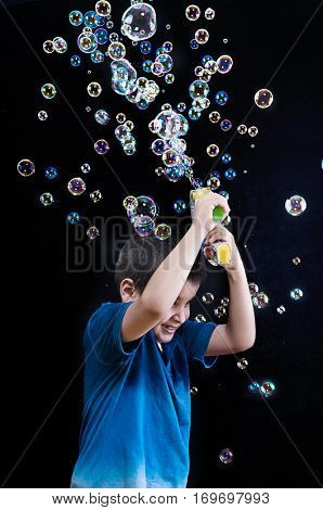 Vertical image of a child playing with soap bubbles over black background.