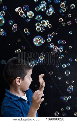 Sweet child child trying to catch soap bubble.