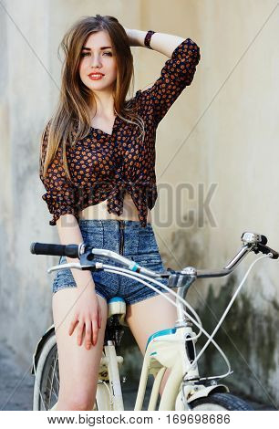 Cute young woman with long straight fair hair wearing on dark blouse and blue shorts is sitting on the bicycle and looking at camera on the street of old European city, waist up