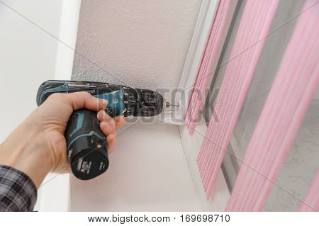 Installing fabric roller blinds. A man drilling holes to fix basis blinds.