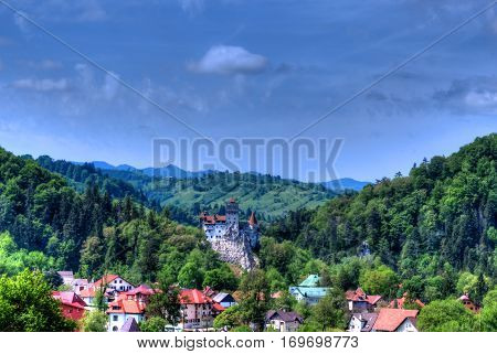 Famous Dracula castle surrounded by medieval architecture in Bran town, Romania
