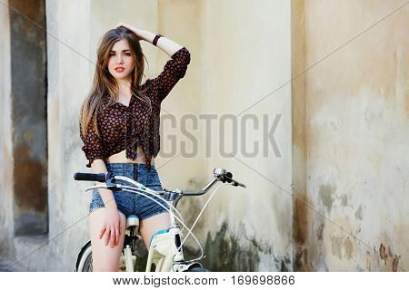 Young woman with long straight fair hair wearing on dark blouse and blue shorts is posing on the bicycle on the old wall background