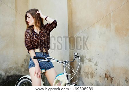 Pretty young woman with long straight fair hair wearing on dark blouse and shorts is sitting on the bicycle on the old wall background