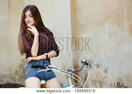 Adorable girl with long straight fair hair wearing on dark blouse and blue shorts is posing on the bicycle on the old wall background