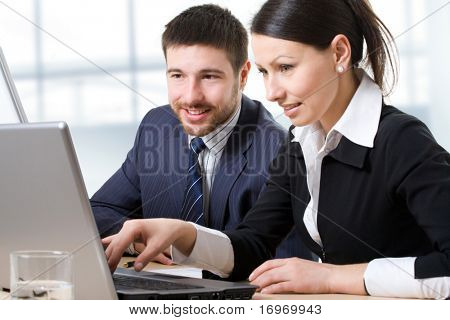 Two businesspeople looking at monitor