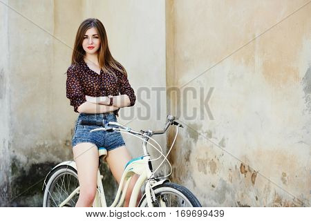 Attractive young woman with long fair hair wearing on blouse and shorts is posing on the bicycle on the old wall background, waist up