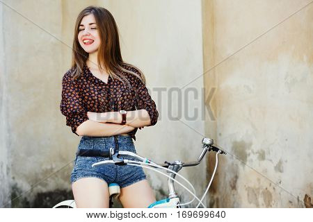 Positive young woman with long fair hair wearing on dark blouse and shorts is posing on the bicycle on the old wall background, waist up