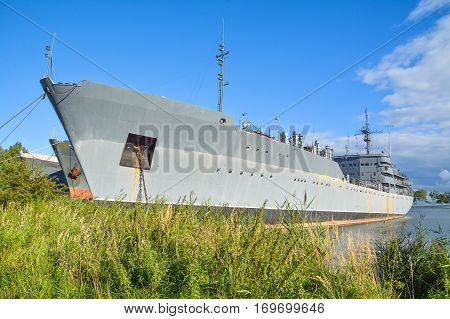 Large  military ship anchored near the shore.