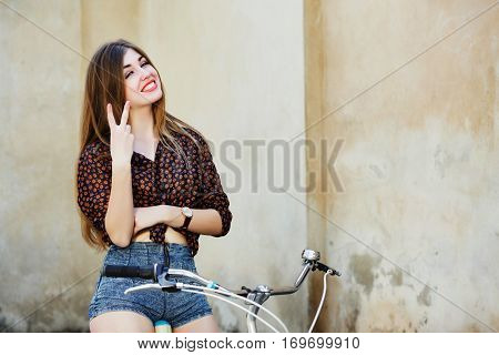 Cheerful girl with long fair hair wearing on dark blouse and shorts is posing on the bicycle on the old wall background, in  the European city, waist up