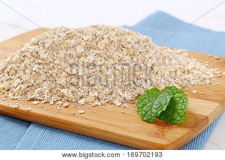 dry rolled oatmeal on wooden cutting board - close up