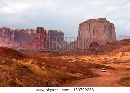 White car driving through  the rocks of Monument Valley park, Arizona