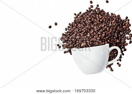 Top view of coffee beans spilling out of a ceramic cup isolated over a white background with room for copy space. Flat lay style.