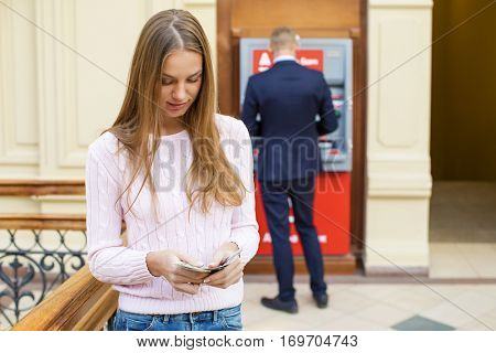 Young beautiful blonde woman is holding a cash dollars on the background of the ATM in a shopping center