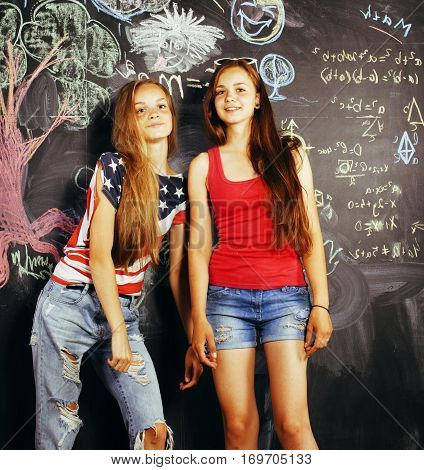 back to school after summer vacations, two teen real girls in classroom with blackboard painted together smiling