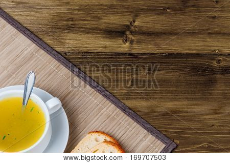 Chicken bouillon with fresh bread in the white bowl. Healthy and tasty food. Beautiful breakfest and dinner. Copy text. Copy space.