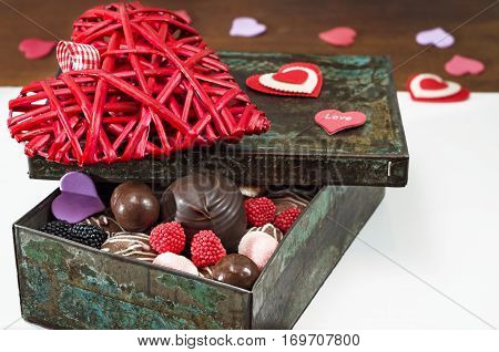 Sweets and decorative hearts for Valentine's day, in an old iron box. Selective focus, close-up.