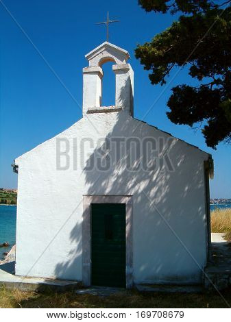 Photo of a little white chaple standing in the shadow of a tree