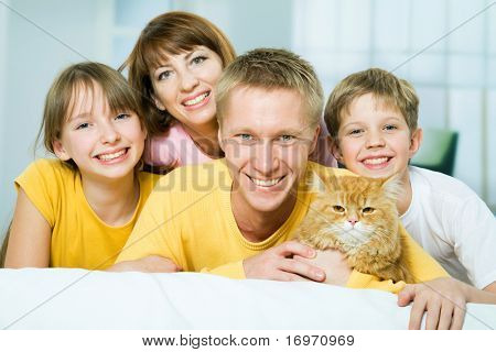 Portrait of a happy family with a house cat looking at camera