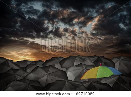 Conceptual image with colorful umbrella among many black ones