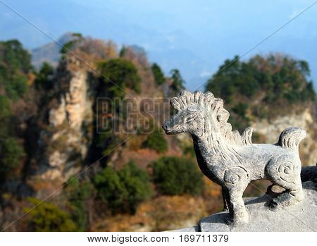 Traditional chinese animal figure on a temple roof on background of Wudang Mountains China