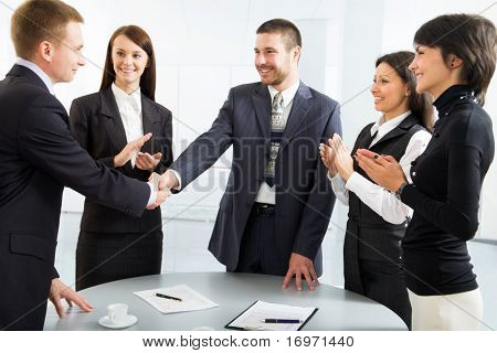 Business colleagues shaking hands and applauding