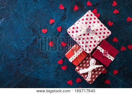 Presents for any holiday concept. Gift boxes frame top view with copy space on darkblue table background. Border of packages for christmas valentine day or birthday