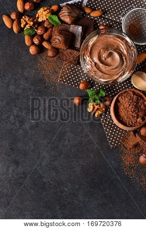 Black food background with cocoa nuts and chocolate paste. top view