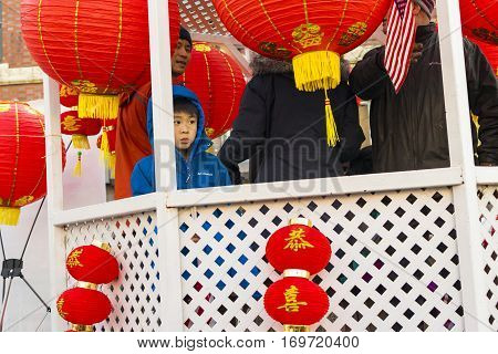 Chicago IL United States - February 5 2017: Yound Asian Boy participates in Chinese New Year parade in Chinatown.
