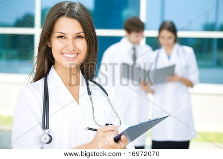 Portrait of a female doctor with two of her co-workers against modern hospital building