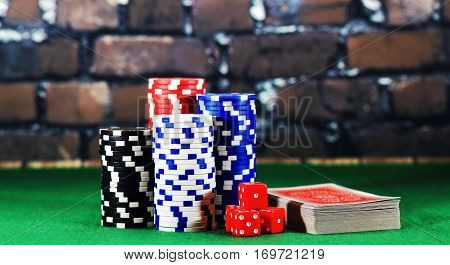 Casino chips cards on green playing table. Games of chance concept. Closeup of color chips and red cards on brick background