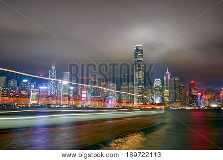 Night view of Hong Kong Island from Kowloon. Boat in motion blur
