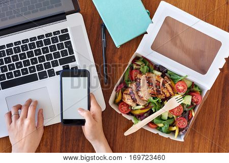 Hands working on laptop computer and ordering food on mobile cell phone app application