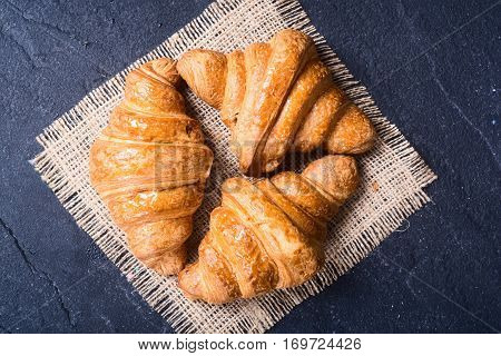 Tasty buttery croissants on stone table .