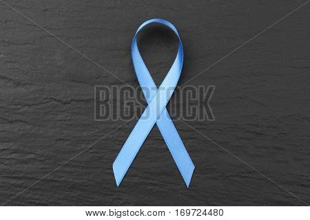 Light blue ribbon on dark textured background. Prostate cancer concept