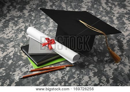 Black graduation cap and diploma on camouflage background