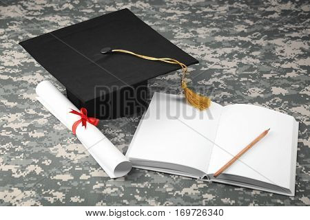 Graduation hat, diploma and book on camouflage background