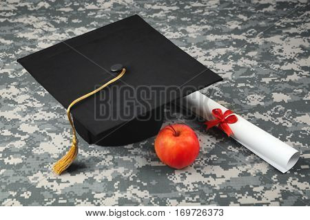 Graduation hat, diploma and apple on camouflage background