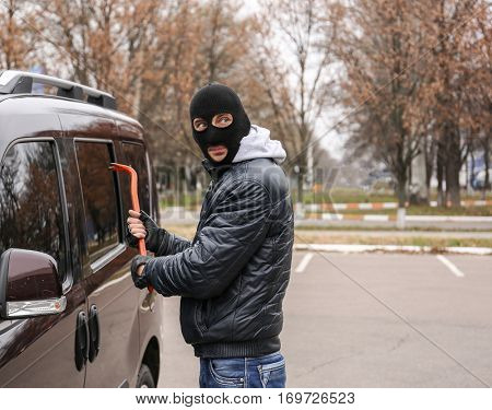 Male thief going to break car window with crowbar