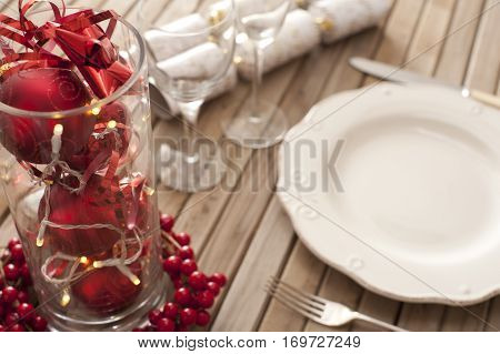Christmas place setting with red themed decorations in a glass container surrounded by colorful red berries with a white empty plate glassware utensils and crackers
