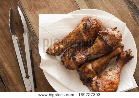 Four delicious marinated grilled chicken legs arranged in a line on paper on a plate with tongs alongside overhead view