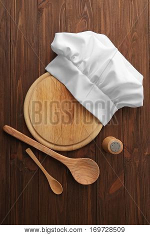 Chef hat, cutting board and kitchenware on wooden background